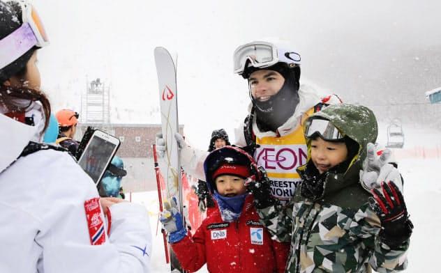 悪天候により男女デュアルモーグルが中止となり、ファンとの記念撮影に応じるミカエル・キングズベリー(23日、たざわ湖スキー場)=共同