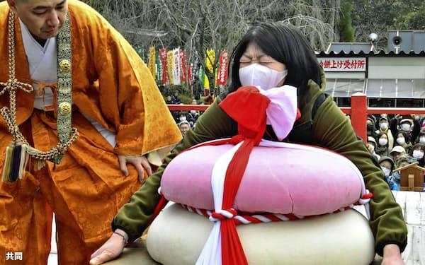 京都・醍醐寺の「餅上げ力奉納」で特大鏡餅の持ち上げに挑戦する女性(23日午後)=共同