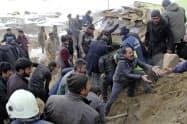 地震の現場で救助活動にあたる人々(イランと国境を接するトルコ東部ワン県、23日)=AP
