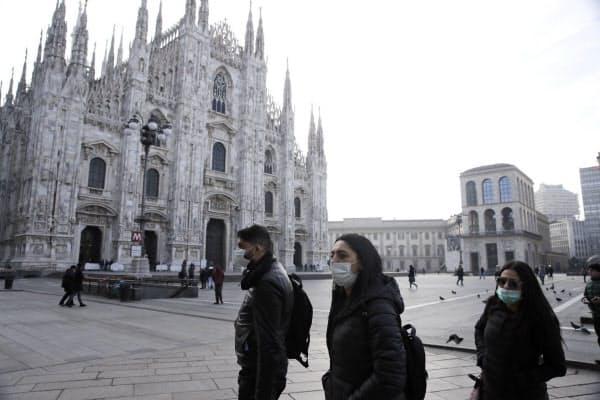 ミラノのドゥオーモ広場でマスクをつけて歩く人々(23日)=AP