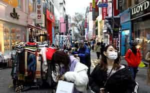 新型コロナウイルスの感染者が急増する韓国のソウルで、マスクをして歩く人々(22日=ゲッティ共同)
