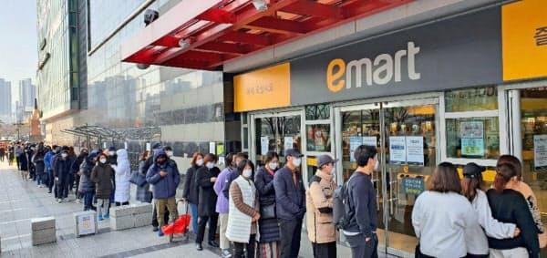 マスク購入のためスーパーの前で行列する人々(24日、韓国・大邱)=聯合・ロイター