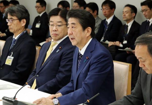 新型コロナウイルス感染症対策本部の会合で基本方針の策定を明らかにする安倍首相(25日、首相官邸)