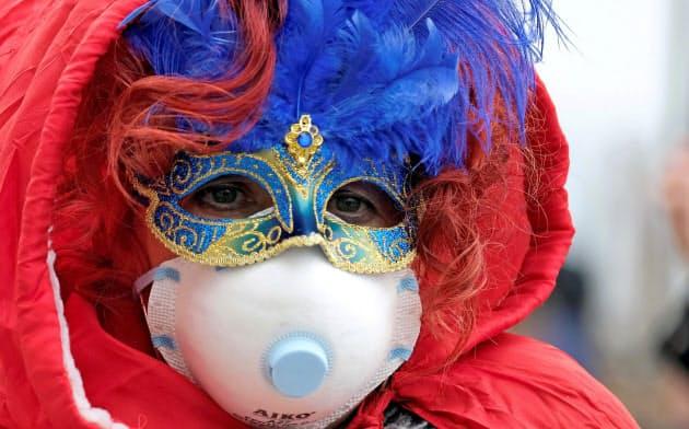 カーニバルのお祭り騒ぎもマスク着用で(23日、ベネチア)=ロイター