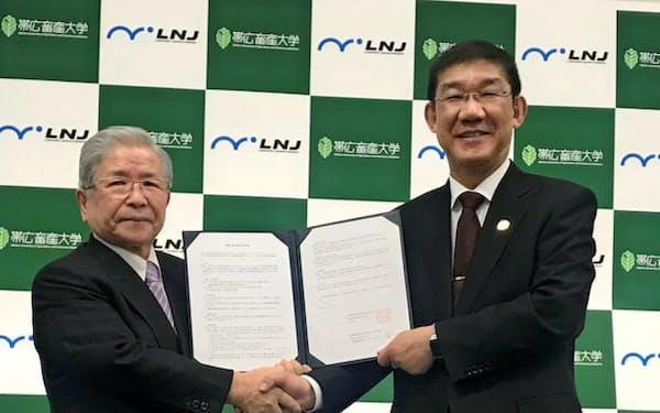 握手する帯広畜産大学の奥田潔学長(右)とロジネットジャパンの木村輝美社長(25日、札幌市)