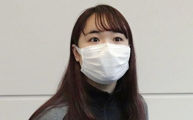 マスク姿で取材に応じる卓球女子の伊藤美誠選手(25日、羽田空港)=共同