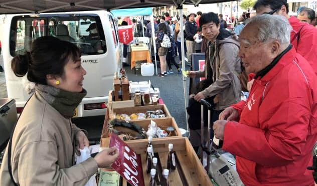 「軽トラ市」全国大会で買い物を楽しむスズキの鈴木修会長(右)(2019年12月、静岡県掛川市)