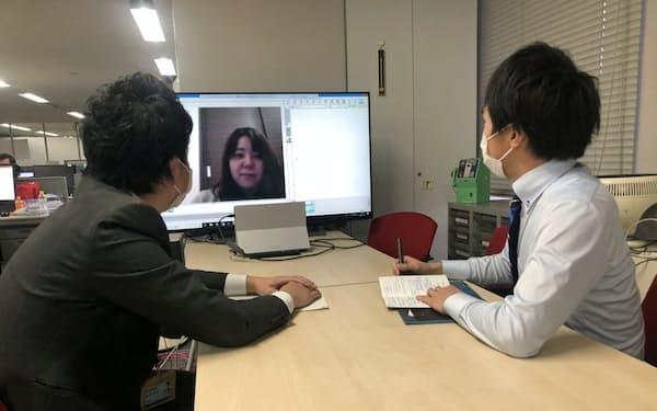 会社から画面を通じテレワークの社員とやり取りするNTT西日本の社員(25日、大阪市)
