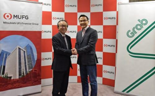 資本業務提携を発表した三菱UFJ銀行の亀沢宏規副頭取(左)とグラブのミン・マー社長(25日、東京・千代田)