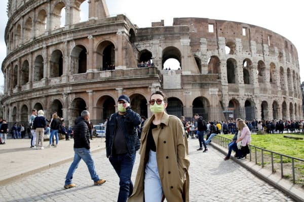 ローマでマスクをつけて歩く人々=ロイター