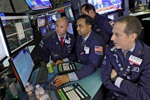厳しい表情で株価の推移を見守る市場関係者ら(25日、ニューヨーク証券取引所)=AP