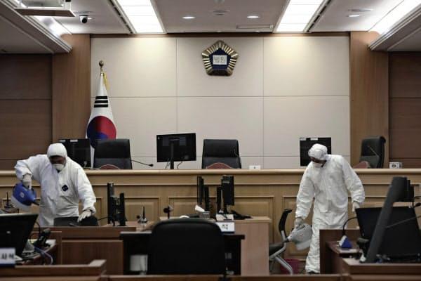法廷を消毒する係官(25日、韓国・光州)=聯合・AP