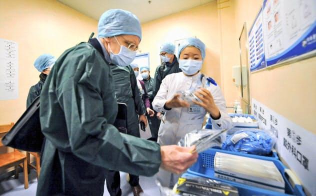 中国・武漢市内の病院を視察するWHOと中国の専門家チームのメンバーら(23日)=共同