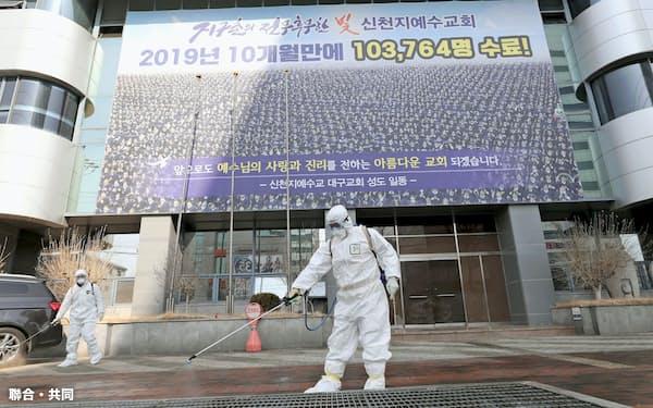 20日、韓国の新興宗教団体「新天地イエス教会」の関連施設で防疫処置を行う保健所関係者=韓国・大邱(聯合=共同)