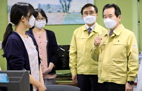 26日、韓国・大邱の病院を訪れ新型コロナウイルスの対策に当たる看護師らを激励する丁世均首相(右端)=聯合・共同