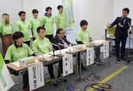 東京都内で記者会見したあしなが育英会の玉井義臣会長(前列左から3人目)ら(26日)=共同