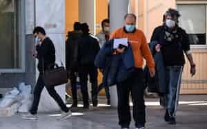 初めての感染者が確認されたギリシャ北部の病院の周辺でマスクをつけて歩く人々(26日)=ロイター-