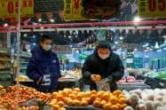 マスクをつけ買い物をする人たち(26日、北京市)=ロイター