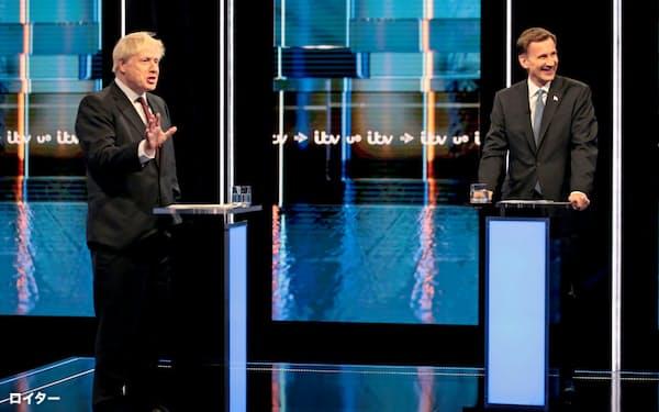 英国の保守党党首選は7週間にわたった(19年7月、討論会で論戦するジョンソン氏(左)とハント氏)=ロイター
