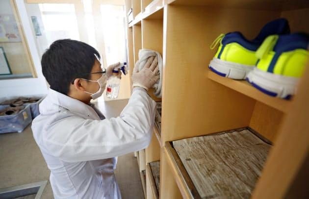 新型コロナウイルス感染拡大の影響で休校となった北海道北広島市の公立小学校で行われた消毒作業(27日午前)=共同