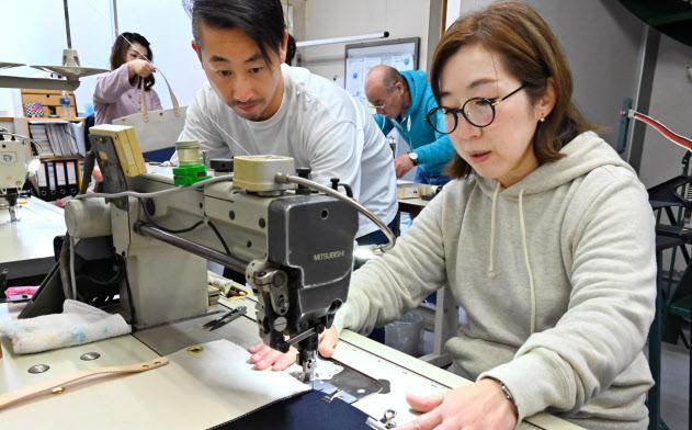 帆布を扱う茂木商工が行うワークショップでトートバッグを作る参加者(右)=東京都荒川区