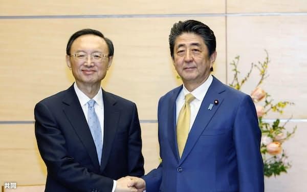 会談前に握手する中国の楊潔篪共産党政治局員(左)と安倍首相=28日、首相官邸
