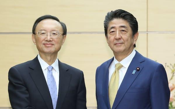 会談を前に中国共産党の楊潔篪政治局員(左)と握手する安倍首相(28日、首相官邸)