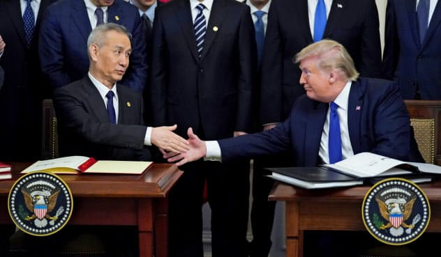 「第1段階の合意」に達し、文書に署名するトランプ米大統領(右)と中国の劉鶴(リュウ・ハァ)副首相(1月15日、ワシントン)=ロイター