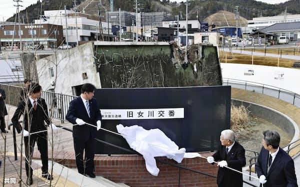 整備が完了した震災遺構「旧女川交番」前で行われた記念式典。左から2人目はパネルを除幕する宮城県女川町の須田善明町長(2月29日、女川町)=共同