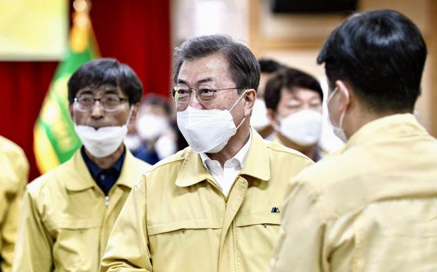 25日、韓国・大邱で開かれた新型コロナウイルスの対策会議に出席する文在寅大統領(中央)=聯合・共同