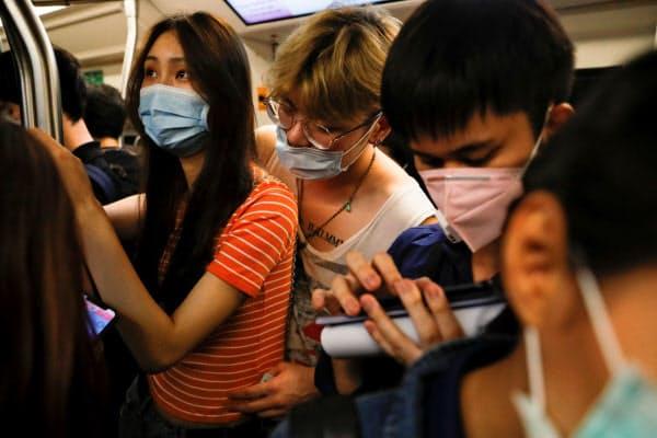 マスクをしてバンコクの高架鉄道に乗る人々(2月26日)=ロイター