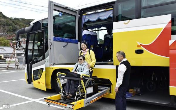 リフトを使って観光バスに乗り込む車いす利用者(1月、佐賀県鹿島市)=共同