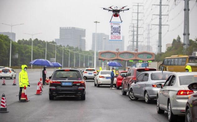 広東省深圳市では市内に入る車両の運転手は、その入口となる高速道路の料金所でドローンがぶら下げているQRコードを自分のスマホで読み取り、登録しなければならない=AP