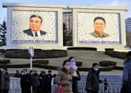 平壌市内に掲げられた故金日成主席(左)と故金正日総書記の肖像画の前を行き交う市民(27日)=共同