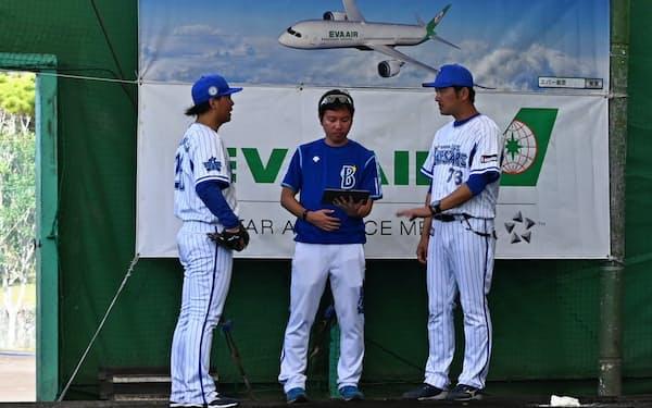 DeNAの沖縄キャンプでタブレットを持ったスタッフを交えてコーチと話す浜口(左)