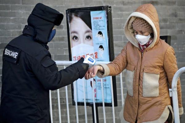中国は繁華街でも歩行者の温度を計測するなど、新型コロナウイルスの感染拡大に警戒を強めている=AP