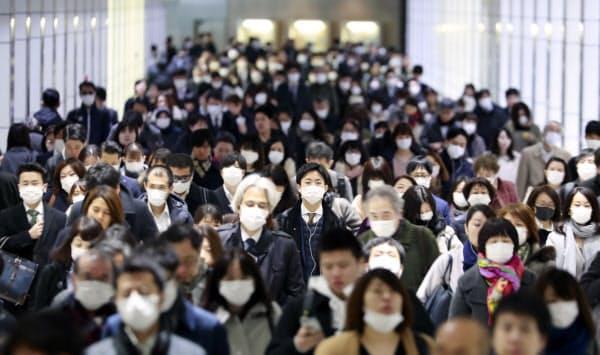新型コロナウイルスを警戒しマスク姿で出勤する人たち(3月4日、東京都新宿区)