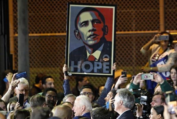 オバマ前大統領のポスターを掲げるバイデン支持者=ロイター