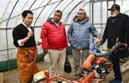 富山県射水市の農場で、母国ネパールからの視察団と話す仏画師のダルマ・ラマさん(左端)=共同