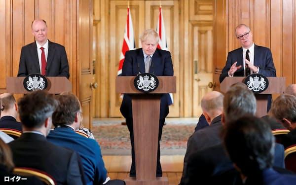 3日、ロンドンで記者会見するジョンソン英首相(中)。左はホイッティ氏、右はバランス氏=ロイター