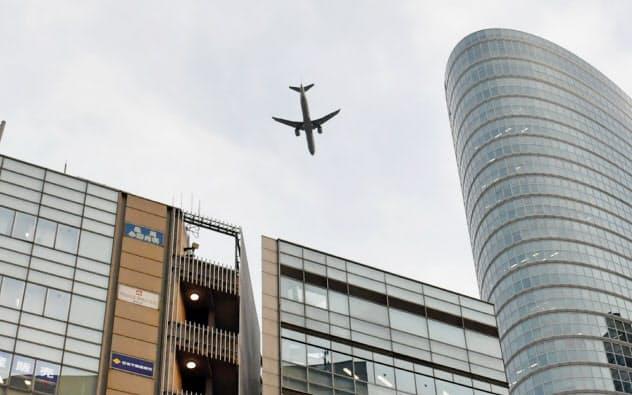 JR品川駅の上空を飛行する旅客機(2月3日、東京都港区)
