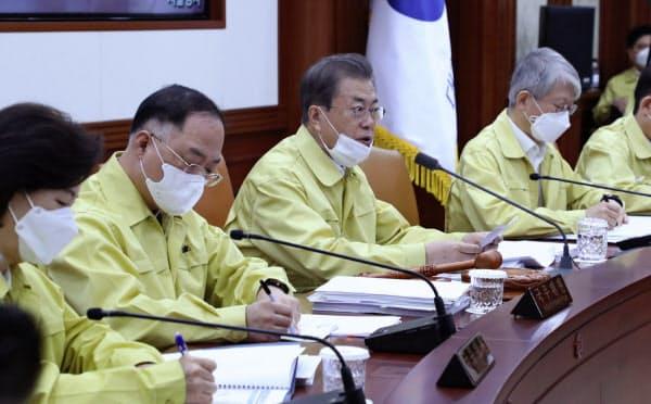 3日の政府の会合で発言する韓国の文在寅大統領(中央)=AP