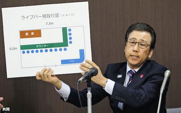 新型コロナウイルスの感染が確認された、繁華街ススキノにあるライブバーの見取り図を手に説明する札幌市の秋元克広市長(7日午後、札幌市役所)=共同