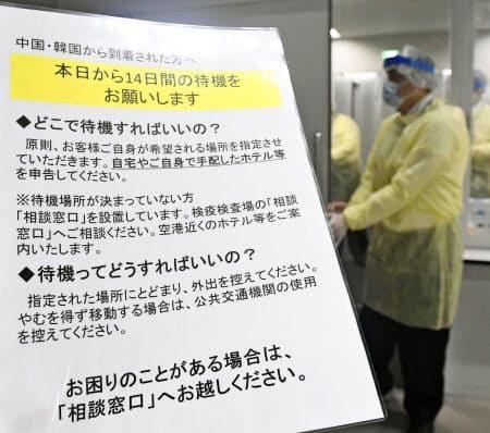 中国と韓国から成田空港に到着した乗客向けに書かれた14日間の待機を求める注意書き=9日午前