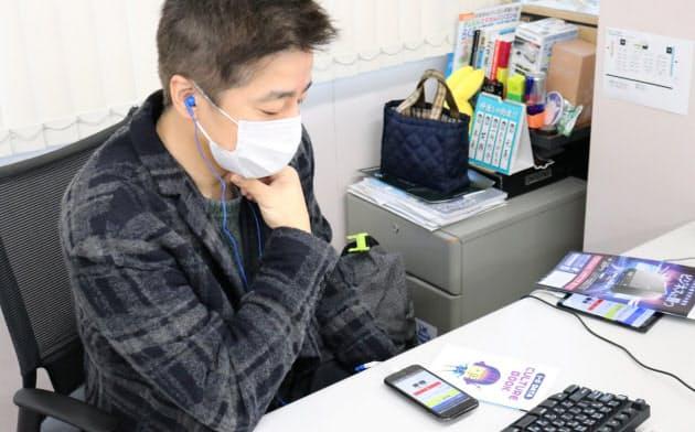 オフィスの自席で朝礼の配信を聞く社員(9日午前、金沢市)