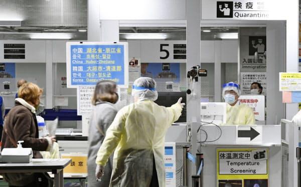 韓国から成田空港に到着した乗客を誘導する検疫官(手前、9日)