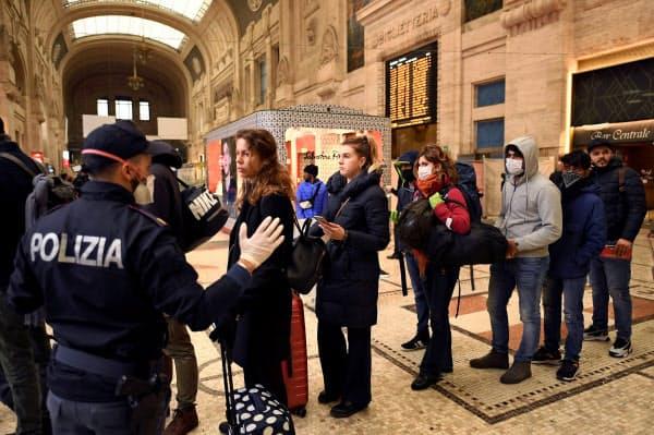 9日、ミラノの主要駅ではマスクをした警官の姿も=ロイター