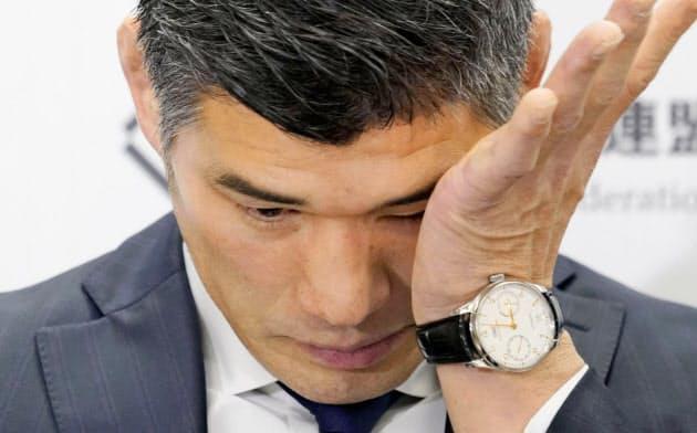 東京五輪代表発表の記者会見で、涙をぬぐう井上康生監督=共同