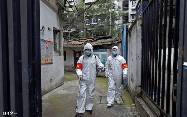 防護服に身を包んで武漢の街を消毒する作業担当者(6日)=ロイター