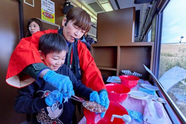 「プレミアムこたつ列車」でホタテ貝の開け方などを教える椎屋さん